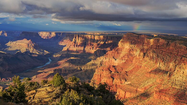 Grand Canyon South Rim at sunset with rainbow in background