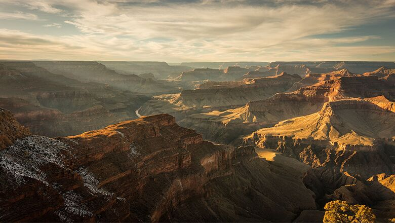 View from the Grand Canyon South Rim during a sunset shining on the canyon walls.
