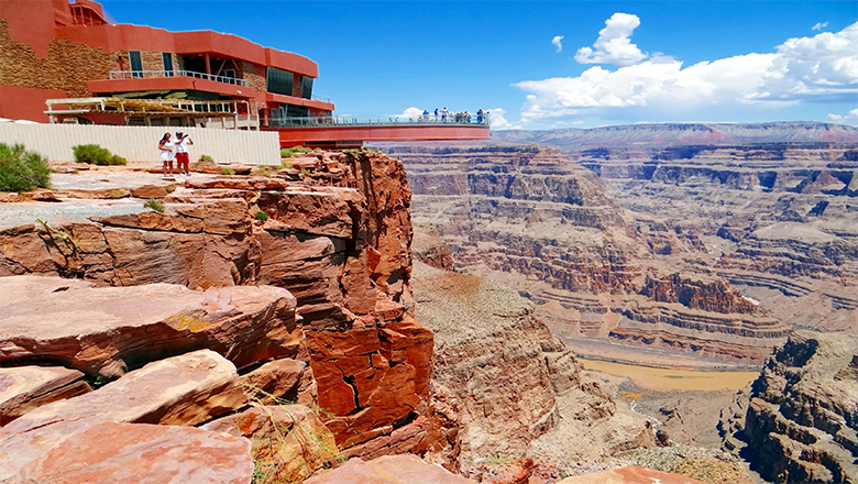 Grand Canyon West Rim with the visitor center and Skywalk in the background on a sunny day.