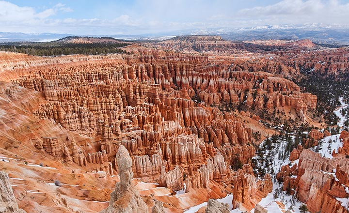 View from the top of an overlook of Bryce Canyon Amphitheater showing red rock spires and towers.