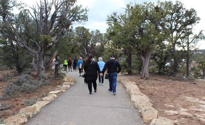 Visitors of Grand Canyon National Park walking along the paved Trail of Time at the South Rim of the canyon.
