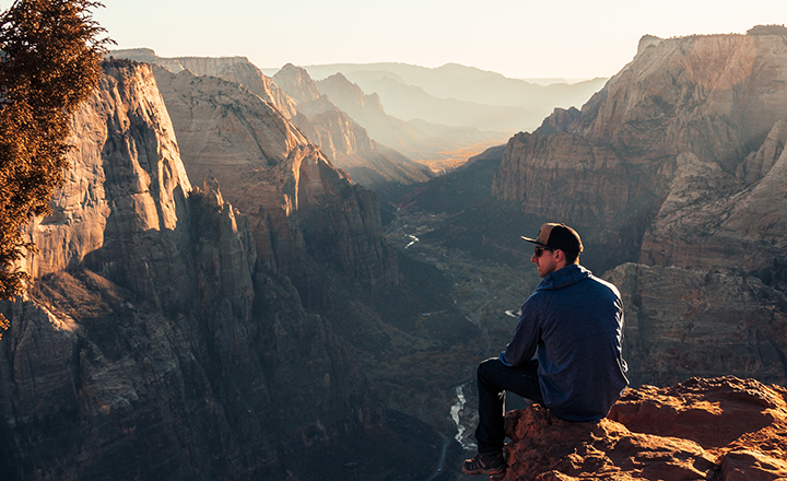 Man sitting on edge of a cliff enjoying the view of Zion Canyon